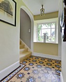 Patterned tiled floor, lattice window and arched doorway over staircase in hallway