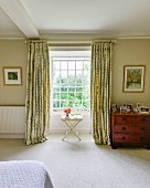 Tray table in front of lattice window with floor-length curtains in bedroom