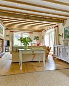 Konsolentisch an Sofa in ländlichem Wohnzimmer mit Holzbalkendecke und elegantem Flair