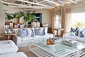 Offener Wohnbereich mit weißen Hussenmöbeln, lackierten Fachwerkträgern in elegantem Landhausambiente