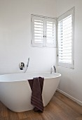 Dark brown towel draped over white free-standing designer bathtub on oak parquet floor below corner windows with shutters