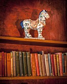 Antique ceramic horse on bookshelf