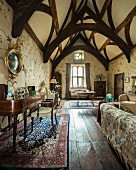 Grosszügiger Wohnbereich mit kunstvoll gebautem Dachstuhl, Wandmalerei und antiken Möbeln