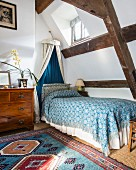 Einzelbett mit gemusterter Tagesdecke und Baldachin vor Dachschräge mit sichtbarer Holzkonstruktion