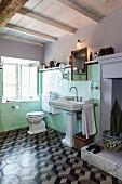 Pastel green wall tiles, pedestal sink and 3D-patterned floor tiles in vintage bathroom