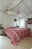 Red and white patterned cover on double bed in bedroom with white wooden ceiling