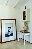 Framed photo leaning against wall, bust and skull on set of white side tables and glass-fronted cabinet on wall