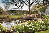 Garten im Frühling mit Teich, Sitzplatz und Glashaus