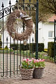 Wreath on wrought iron gate and baskets of spring flowers