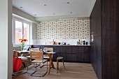Cantilever chairs around dining table in kitchen with dark brown cabinets and retro floral wallpaper