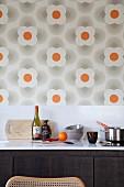 weiße Küchenarbeitsplatte mit Kochutensilien vor Spritzschutz- Streifen und Retro Blumentapete an Wand