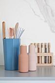 Küchenzubehör in Pastelltönen vor einer Marmorwand