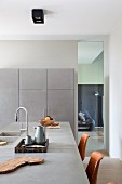 Kitchen counter with concrete worksurface and integrated sink, pale grey fitted cupboards along one wall next to floor-to-ceiling interior window with view into living room