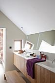 Minimalistische Waschtischzeile mit zwei Waschbecken und schräg gestelltem Wandspiegel unter Dachschräge