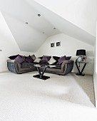Corner sofa under sloping ceiling with recessed spotlights in elegant minimalist interior