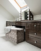 Upholstered trunk seat in front of custom sideboard with vanity mirror under skylight