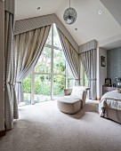 Pale leather easy chair and matching footstool next to glass wall with draped curtains and pelmet in elegant attic bedroom