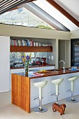 White, designer bar stools at free-standing kitchen counter with wooden top and sides in open-plan kitchen