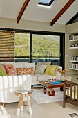 Pale sofa with patterned scatter cushions against balcony window with view in modern living room