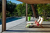 Sun loungers with pale cushions and bolsters on large wooden terrace with roof