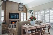 Loungebereich, Konsolentisch aus Holz mit Schnitzereien vor Rückseite eines Sofas, gegenüber Flachbildschirm an hellbraun getönter Wand
