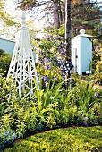 White obelisk in flowering bed of Brunfelsia and purple perennials