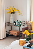 View across coffee table to vase of yellow flowers on retro serving trolley in corner of living room