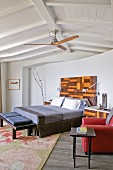 Double bed with headboard, side table, red leather armchair and ceiling fan in attic room