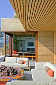 Sofa set around colourful hearth on terrace outside house with façade clad in wooden laths