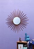 Round mirror surrounded by sunburst made from chopsticks on lilac wall