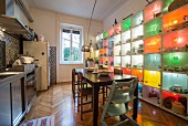 Dining area between stainless steel kitchen counter and colourful, illuminated shelving system holding crockery and kitchen utensils