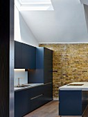 Kitchen with exposed brick wall and skylight