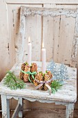 Lit candles in candle holders made from pine cone bundles tied with checked ribbons