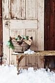 Metallkorb mit Zapfen und Christbaumkugeln vor einer alten Tür