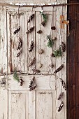 Mobile made from various conifer cones and twigs hung on old door
