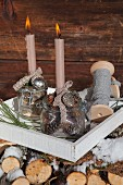 Advent arrangement of two lit candles in vintage-style preserving jars against rustic wooden wall