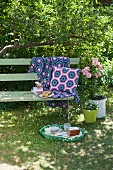 Crocheted cushions and blanket on garden bench and tray of cake on lawn