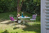Crocheted cushions on white metal chairs around set table in summery garden