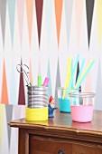 Blechdose und Gläser mit Luftballons dekorativ überzogen zur Aufbewahrung von Trinkhalmen und Schreibutensilien auf Antikkommode