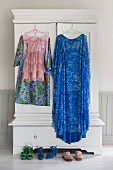 Dresses hung from clothes hangers on doors of white wardrobe