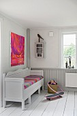 Rustic white bench with brightly coloured seat cushion below modern artwork in corner