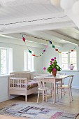 Pink-painted chairs, table and bench below windows and colourful garland in corner of rustic room