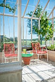Red garden chairs and small table made from terracotta pot in conservatory with gravel floor