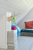 White, wood-clad attic room with stylised hunting trophy on wall and colourful covers and pillows on bed in background