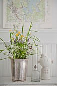 Silver vase of wildflowers, oil lamp and ornament in front of map of Sweden