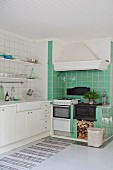 Kitchen counter with white base cabinets and wrought iron cooker and extractor hood in green-tiled cooking area
