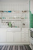 Sink on white base units below tiled wall and bracket shelves in kitchen