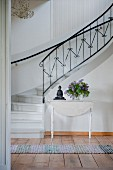 Vase of lilac and Buddha figurine on white wooden table at foot of winding staircase with delicate wrought iron balustrade in foyer