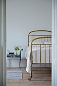 Brass bed on casters and vintage bedside table seen through open door