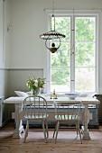 Essplatz mit hellgrauen Stühlen um Vintage Tisch vor Sprossenfenster